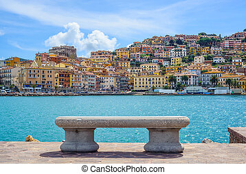 Bench on seafront in Porto Santo Stefano harbor, Monte...