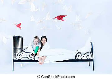 nursery - Cute kids sitting together on the bed under the...