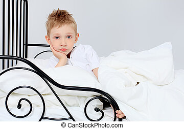 time to sleep - Cute little boy is going to sleep in a bed.