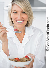 Happy woman eating cereal for breakfast looking at camera