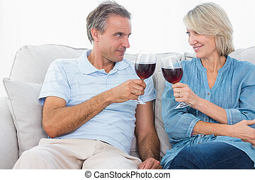 Couple toasting with red wine on the sofa at home in living...
