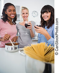 Happy friends making spaghetti dinner together and drinking...