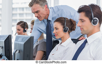 Manager helping call center agent on a computer
