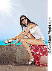 girl sits on quay