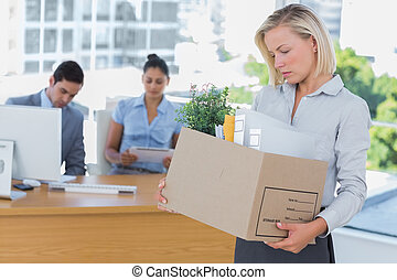 Sad businesswoman leaving office after being let go