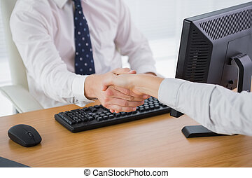 Businessman shaking hands with a co worker at his desk in...