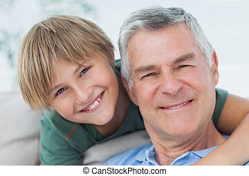 Portrait of grandson hugging grandfather sitting on the...