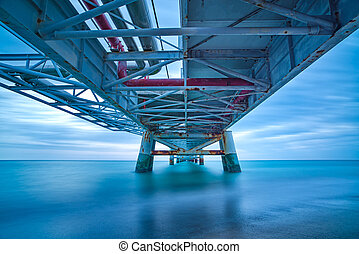 Industrial pier on the sea. Bottom view. Long exposure...