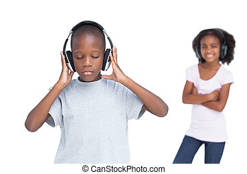 Little boy with eyes closed listening to music with his...