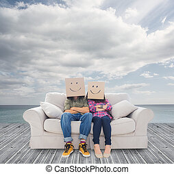 Couple sitting on couch with cardboard over their head -...