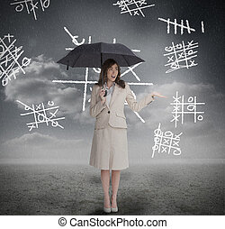 Businesswoman with noughts and crosses holding umbrella and...