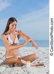 Smiling woman sitting on beach applying sunscreen - Smiling...