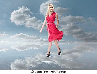 Fashion woman walking on a puddle - Fashion woman wearing a...