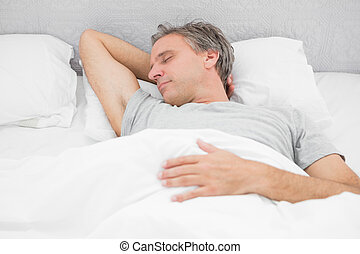 Man sleeping soundly in his bed at home