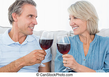 Couple toasting each other with red wine on the sofa at home...