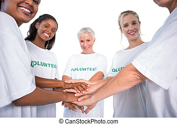 Group of female volunteers with hands together smiling at...
