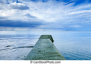Concrete pier or jetty on a blue sea and cloudy sky...