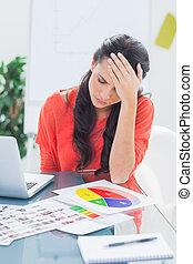 Annoyed designer sitting behind her desk