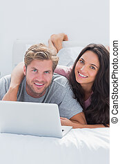 Happy woman embracing husband while using a laptop