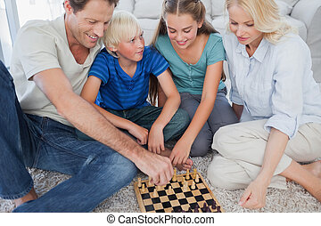 Portrait of a cheerful family playing chess lying on a...