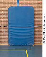 Large blue mat strapped to a brick wall, gym