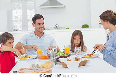 Family eating pasta with sauce for the dinner