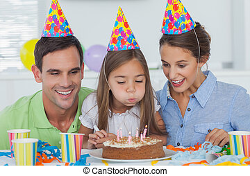 Little girl blowing out her candles with her parents