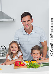 Portrait of a father and his children in the kitchen while...