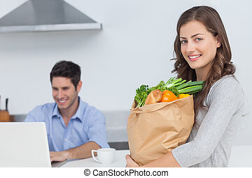 Woman holding groceries bag while her husband is on his...