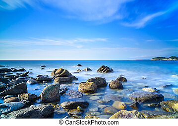 Baratti bay, rocks in a blue ocean on sunset. Tuscany,...