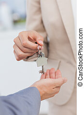 Estate agent giving house key to a client