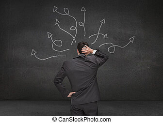 Doubtful businessman looking at arrows drawn on a grey wall