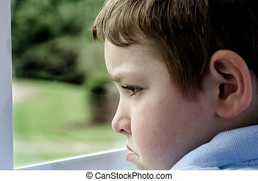Sad child looking out window on gloomy day
