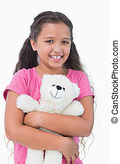 Cute little girl holding her teddy bear on white background