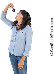 Brunette with her microphone singing on white background