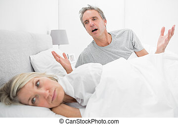 Man pleading with his upset partner in bed at home in...