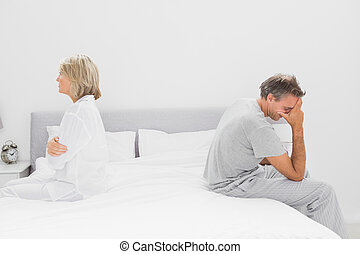 Couple sitting on opposite sides of bed after a dispute