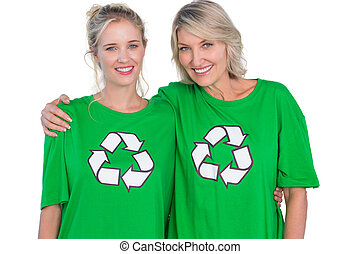 Two smiling women wearing green recycling tshirts on white...