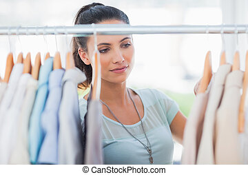 Attractive woman looking at clothes in a studio