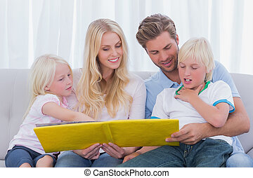 Happy family reading a story together on the couch