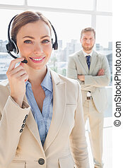 Smiling call centre agent with colleague behind her