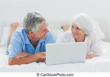 Couple lying and using a laptop pc in bed - Mature couple...