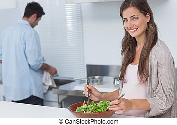 Woman mixing a salad in the kitchen while her husband is...