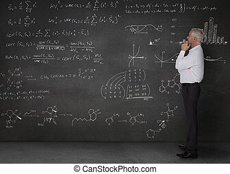 Elegant businessman looking at maths equations written on a...
