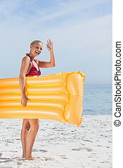 Smiling woman waving and holding lilo on beach