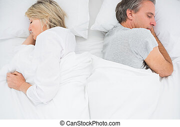 Couple sleeping back to back at home in bed