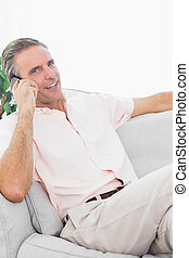 Man on his couch making phone call smiling at camera
