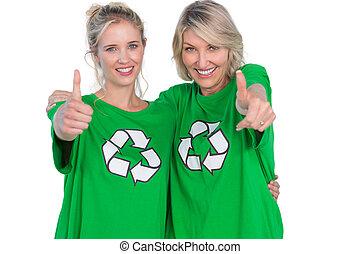 Two smiling women wearing green recycling tshirts giving...