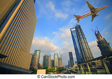 Aircraft flying over the modern city buildings over -...