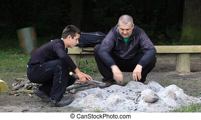 Father and son piling firewood for campfire episode 5